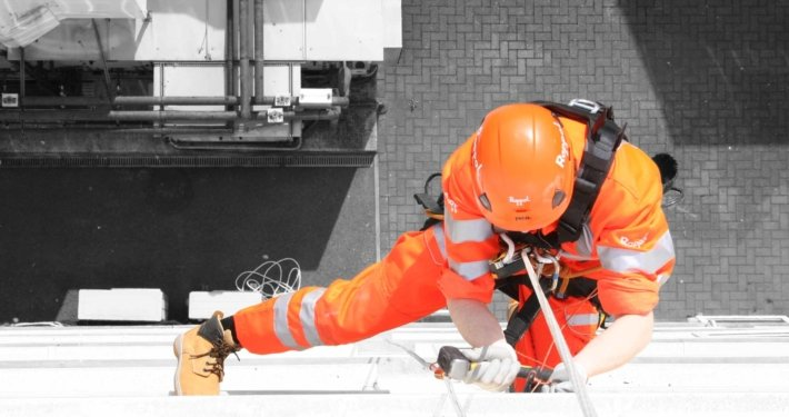 View of a Rappel rope access technician undertaking high level building maintenance works