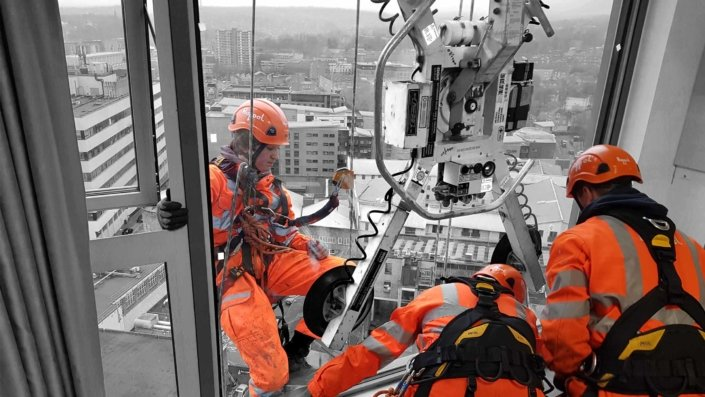 Rappel rope access team installing high level window glazing units