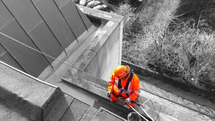 Rappel rope access technician undertaking gutter and drainage maintenance works