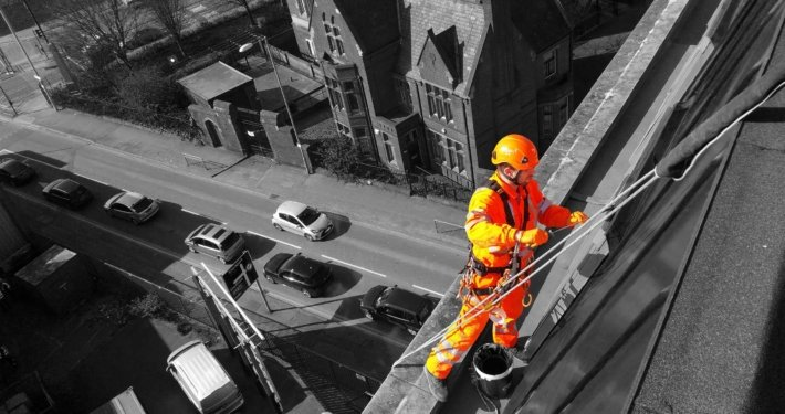 Rappel rope access technician undertaking high level building painting